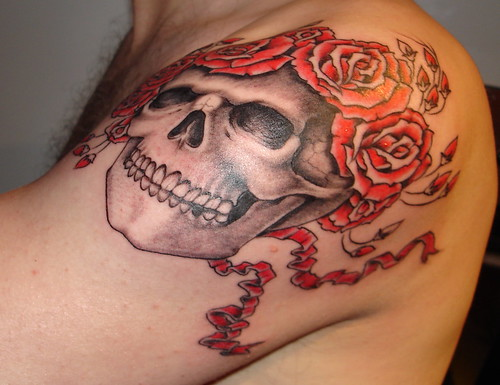 Demonic skull tattoo symbols with rose criss-crossed being inked on upper