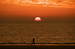 Walking by the Sun (nippak) Tags: ocean sunset sky orange sun beach nature yellow walking healthy spain nikon europe skies andalucia cadiz jogging d300 cloudis