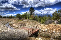 Canal Footbridge (Thad Roan - Bridgepix) Tags: bridge blue trees sky mountain snow water clouds landscape canal rust scenery colorado rocks footbridge steel rusty pedestrian explore buenavista wikipedia fourteener hdr arkansasriver bridging collegiatepeaks mountprinceton chaffeecounty photomatix 200805 bridgepixing bridgepix johnsonvillage