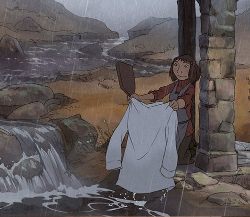 """L'illusionniste""'s Alice, a small, blunt-cut-brown-haired girl with dark clothes and an apron, washes a white shirt in a lake while it rains. Image via empireonline.com."