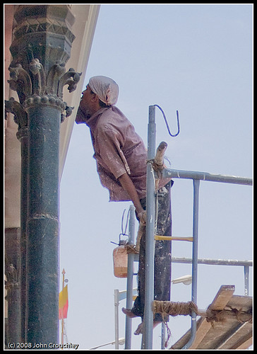 Painter perched on scaffolding