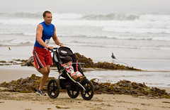 Man running while pushing a baby trike - Runne...