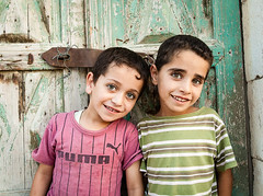 Two Jordanian boys stand in front of door (damonlynch) Tags: door old boy people building cute male eye smile smiling architecture youth standing outside outdoors person stand eyes rust doors exterior child architecturaldetail outdoor body masculine innocent middleeast entrance structures architectural jordan doorway human arab rusted worn lad portal exit activity juvenile humanbeing youngman jordanian portals humans activities middleeastern humanbeings edifice edifices ajloun 412yearsold ajloungovernorate baoun