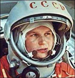 Tereshkova, a young white woman, in a space helmet and orange jumpsuit