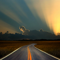 Another Sunset Down the Road (Carlos Gotay Martnez) Tags: road sunset sky mountains field grass clouds bravo solitude rays curve lightrays abigfave aplusphoto karmanominated