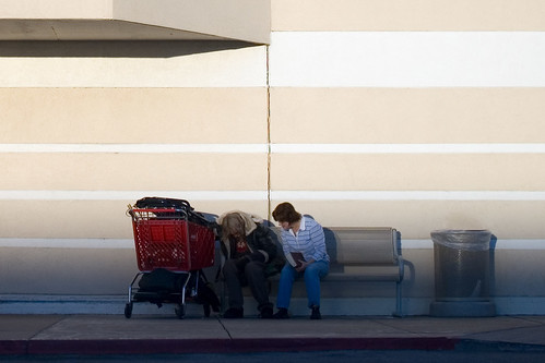 boy with book talking to a homeless man outside Target