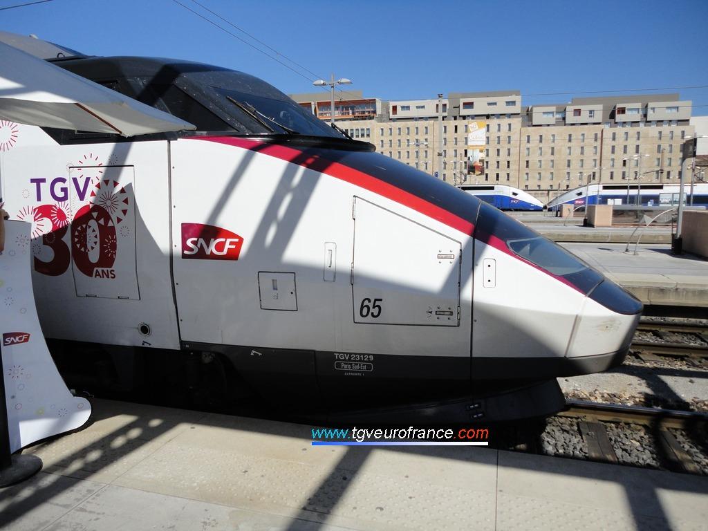 Vue de profil de la motrice impaire (23129) de la rame TGV Sud-Est 65 stationnant voie A dans la gare de Marseille Saint-Charles