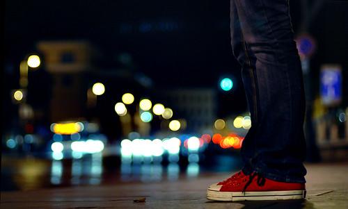 Fotografía de unas piernas con unas Converse All Star rojas con un montón de luces de coches, farolas y semáforos al fondo en plena noche