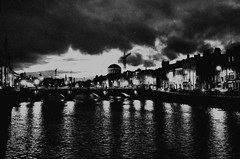 Dublin Rain Clouds (MacGBeing) Tags: ireland sunset blackandwhite bw dublin white black slr film wow reflections twilight noir moody cityscape noiretblanc cloudy streetlights grainy darkwater blanc canoneos5 badweather filmnoir riverliffey darksky darkdays ilfordxp2400 poorlight filmphotography fourcourts riverreflections 50mmf18ii grattanbridge dramaticweather darkriver irishweather dramaticimage sungone streetlightreflections liffeyreflections dikensianskyline