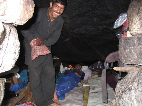 Our porter smiles as Ashok (guide) rests in the rock shelter/kitchen