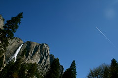 falling/flying (Doubletee) Tags: california blue trees sky yosemitefalls water clouds geotagged nationalpark contrail kitlens yosemite granite yosemitenationalpark yosemitevalley ynp upperyosemitefall canonefs1855mmmf3556
