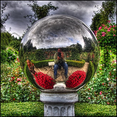 pausing for a moment of reflection (ecstaticist) Tags: family flowers red sky cloud canada reflection tree glass rose metal stone photoshop ball garden fun bravo bc cloudy pillar lawn dramatic manipulation victoria tourist casio vancouverisland sphere hedge shrub drama hdr butchart attraction hdri topaz adjust exf1
