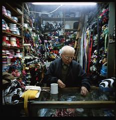Elderly man in his store (Son of Lumiere) Tags: street portrait people 120 6x6 film colors shop mediumformat colorful market interior hellas oldman hasselblad greece thessaloniki fabrics swc kodakportra400nc autaut zeissbigon38mmf45