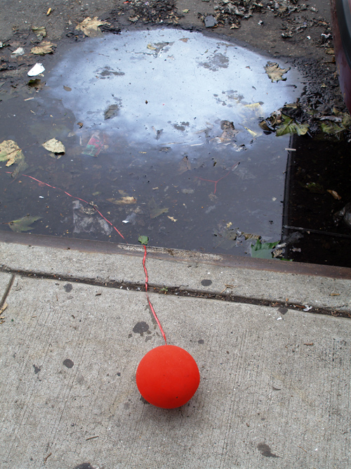 red balloon on sidewalk with oily puddle, Manhattan, NYC