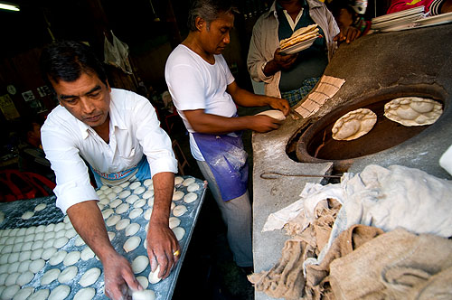 Baking bread in a tandoor oven at a Muslim restaurant in Mae Sot