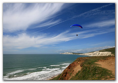 Paragliding, Compton Bay, Isle of Wight. Into the wild blue yonder (s0ulsurfing) Tags: ocean blue light sea sky cliff cloud sunlight seascape tourism praia beach nature water weather sport clouds danger downs fun island bay coast mar flying scary skies play natural bright wind action compton patterns extreme flight wide wing perspective shoreline wideangle cliffs coastal shore isleofwight coastline paragliding gliding glider hanover paraglider 2008 landschaft isle olas channel englishchannel wight cirrus paraglide l