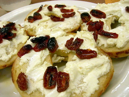 Cheese bagel with goat cheese and dried tomatos in olive oil