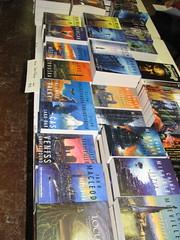 Piles of books stacked on the table, all with Edward Miller covers