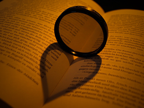 Heart shaped shadow cast over a book by a round lens