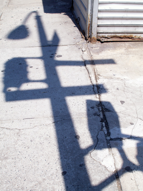 lamppost shadow on Manhattan sidewalk, New York City, NYC