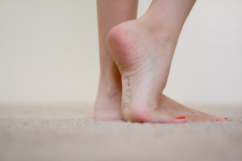 Fotografía de unos pies de chica con las uñas pintadas de rojo en el que en la planta del pie derecho está escrito I love you