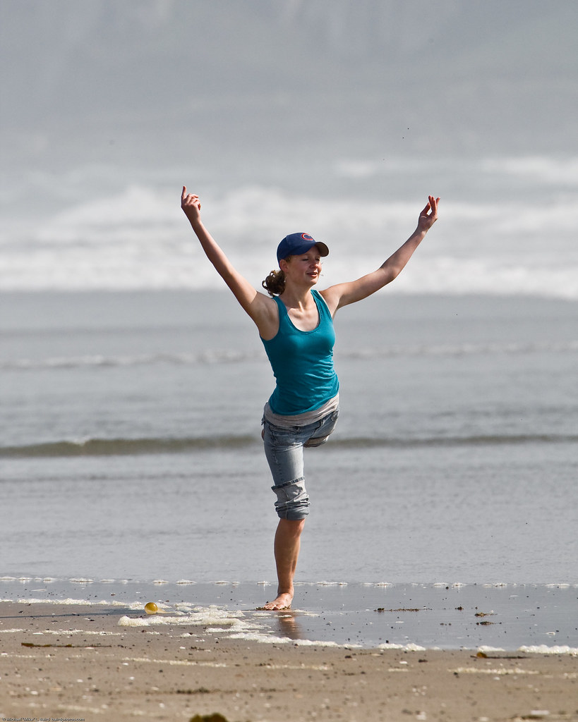 7 of 8 Girl dances at water's edge on Morro Strand State Beach