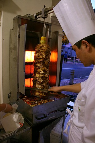 Doner kebab - chef carving grilled meat off a vertical spit