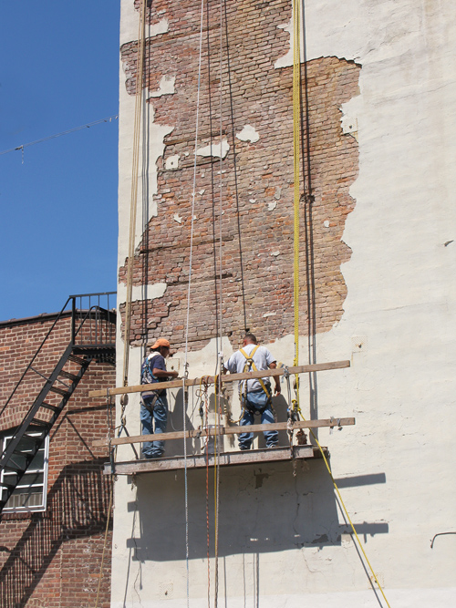 men work on a wall