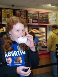 a girl happily bites into a donut while wearing a blue shirt with pictures of fetuses on it