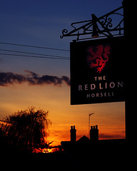 Red Lion At Night (ElWanderer) Tags: uk sunset red chimney england sky orange tree silhouette sign yellow restaurant evening woking pub photoshopped review silhouettes highcontrast surrey chimneys reviews pubsign redlion settingsun publichouse horsell restaurantreview canonef50mmf18ii clearpicturestyle wowiekazowie