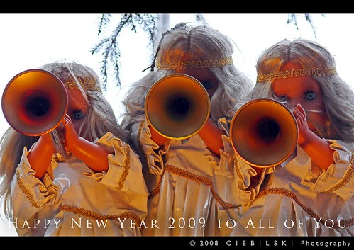 3 angels blowing trumpets with branches from pine tree in the background, captioned Happy New Year 2009 to All of You (c) 2008 CIEBILSKI Photography (released under Creative Commons Attribution / Non-Commercial License)