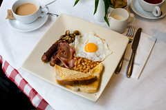 outrageous propaganda! (lomokev) Tags: food breakfast canon mushrooms eos milk bacon beans brighton tea folk egg knife sausage plate 5d friedegg fryup opposition fullenglish canoneos5d oppositioncafe file:name=img2357