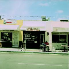 Hair City Barber Shop (Brian Auer) Tags: california street people sunlight color film outside xpro sitting unitedstates sandiego kodak outdoor crossprocess 120format streetphotography naturallight slidefilm sidewalk barbershop sit littleitaly asa100 75mm minoltaautocord ektachromee100vs