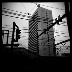 Tokyo Reddux (gullevek) Tags: sky blackandwhite building 6x6 japan train geotagged tokyo fuji iso400 wires electricity   signal  shinkansen housebuilding holga120cfn    fujineopanpresto400 epsongtx900 geo:lat=35654585 geo:lon=139756994