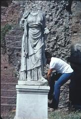 American climbs statue at Roman Forum, 1982
