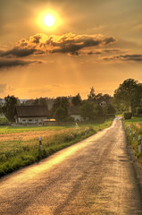 Sunset road (Tambako the Jaguar) Tags: road houses sunset orange grass clouds landscape switzerland nikon bravo village view farm gradient fields rays straight zrich tones hdr d300 photomatix platinumphoto anawesomeshot impressedbeauty aplusphoto goldstaraward pathscaminhos flickrlovers brschweid nikonflickraward grouptripod