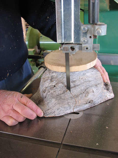 wood burl being cut on a bandsaw to make it round, for woodturning on a lathe