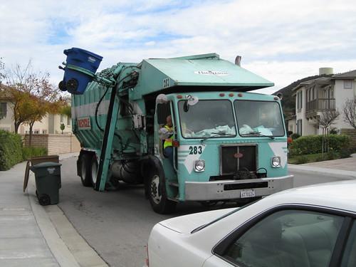 垃圾車的機械手臂準備放下垃圾桶