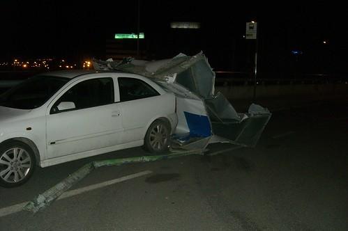 imagen foto de panel publicidad acartonado por el golpe del viento contra un coche en Esplugues