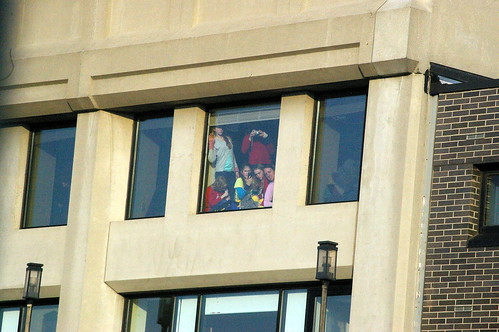 A family in the hotel across the street, trying to see the parade