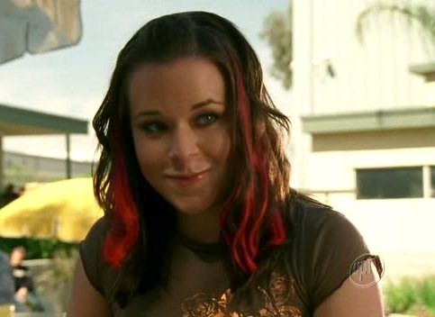 Mac, played by Tina Majorino, smiles slightly. She is a white woman with wavy brown hair with bright red streaks in it and blue eyes. She is wearing a short-sleeved olive green t-shirt and is outdoors on a sunny day; the high school cafeteria, with yellow umbrellas over tables, is out of focus in the background.