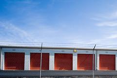 Five (willstotler) Tags: orange fence doors cosina 15 storage barbedwire m8 voightlander ultrawide heliar cv15 selfserv leicam8 skyleica selfservicestorage