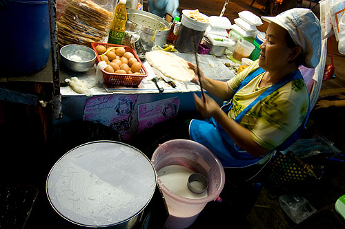 Making khanom paak mor, Vietnamese-style steamed noodles, at Mukdahan's evening market