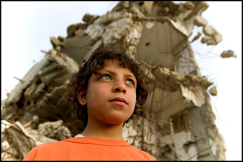 Palestinian child stands in front of the rubble of a home destroyed by an Israeli missile. March 2006, From ImagesAttr
