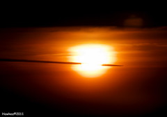 They have pierced the sun.... (Hawkea) Tags: sunset sky sun plane canon airplane flying trail eos500d hawkea rebelkissx3