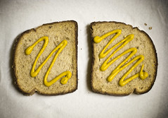 Mustard On Bread (Wade Griffith) Tags: stilllife food yellow bread 50mm wheat papertowel mustard crumbs f18 simple wadegriffith2010