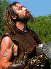 Viking Warrior (Vineyards) Tags: portrait cinema man male sunshine tattoo museum beard weekend retrato profile helmet nederland thenetherlands battle eindhoven portrt norman sweat warrior historical timetravel pause scandinavia vikings viking portret movieset 2008 scar ritratto reenactment sunbathing brabant helm tatuaggio tatuaje rievocazionestorica lowangle tatuagem openluchtmuseum tatovering livinghistory tatouage geschiedenis historisch vikingo baard wikinger pinksteren ttowierung tatoeage tatuering vichinghi vikingar recreacinhistrica vikingen levendegeschiedenis tijdreizen vikingweekend krijger aplusphoto reconstitutionhistorique recriaohistrica historisktterskapande wikingkrieger