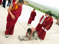 Tibetan Buddhist Monk tries out the skateboard at the Arou Buddhist Temple in Arou, Qinghai Province, China