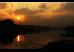 Sunrise over the river (SenShots / Senthilmani's Photography) Tags: morning travel blue trees sunset sky orange sun india white man reflection green tower nature water colors beautiful grass silhouette yellow fog sparkles clouds sunrise canon reflections river dark skyscape landscape photography mirror evening boat early scenery colorful earth lakes scene shades m environment greenery rays lighter lovely rise shape goodmorning naturally southindia brighter beautifulearth shadwos senthil msenthil platinumphoto theunforgettablepictures rubyphotographer souhtindia senshots armsenthil senthilmani senshotsphotography senshots2008