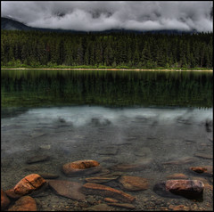 Calm Under Low Cloud (ecstaticist) Tags: park travel trees cloud lake holiday canada reflection tree water rain rock reflections dark circle sand cabin exposure jasper five ripple shoreline drop calm resort national shore alberta droplet transparent flotsam patricia hdr oppressive 5x photomatix tonemapped tonemapping logsky
